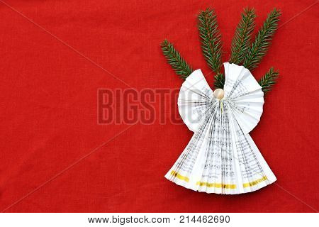 angel folded with paper on red cloth with spruce branches