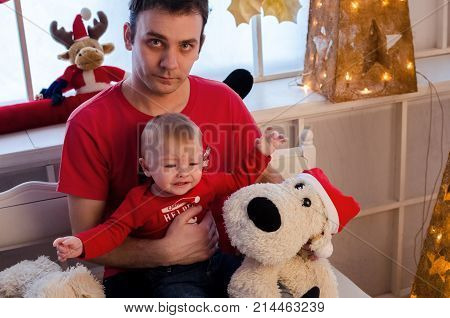 Father with an upset expression on his face holding his crying baby. Family in red clothes in Christmas time. Merry Christmas and Happy New Year. Baby first Christmas.
