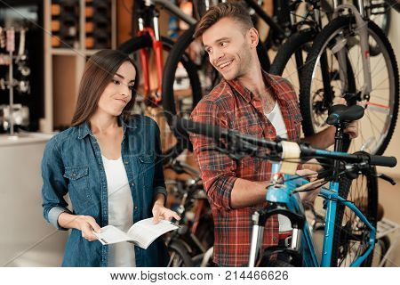 A young couple came to the bicycle shop to choose a new bicycle. A man and a woman look attentively at different bicycles and details. The girl looks skeptical.