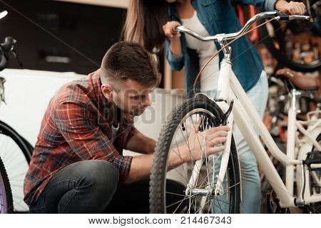 A young couple came to the bicycle shop to choose a new bicycle. A man and a woman look attentively at different bicycles and details.
