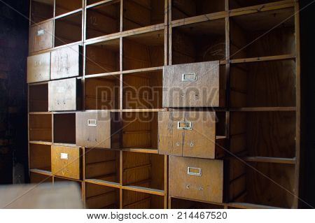 A forgotten empty document cabinet. Old damaged office wardrobe case with open drawers.
