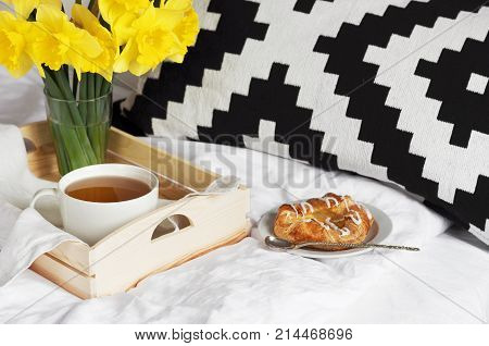 Wooden tray with light breakfast and flowers on white textile in bed. Herbal tea Breakfast in bed Morning Yellow daffodils.