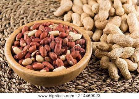 Wooden bowl of peeled peanuts and peanuts in nutshell on natural matting