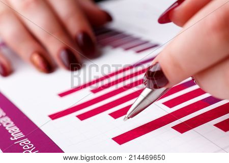 Female arm hold and point silver pen in financial graph solve and discuss problem closeup. Fresh view at situation board council sale adviser examine advisor profit audit job market irs inspector