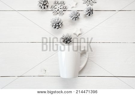 Mockup white cup with christmas cones and stars, on a white wooden background. Flat lay, top view photo mock up.