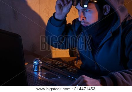 surprised hacker looks at the laptop, the intruder breaks into a system, the concept of web crimes