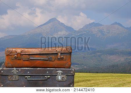 Vintage Travel Suitcases Over Mountain Landscape