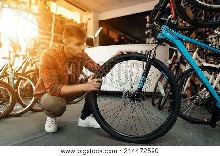 A young guy examines a wheel from a bicycle. He came to the bicycle shop. He looks very closely.