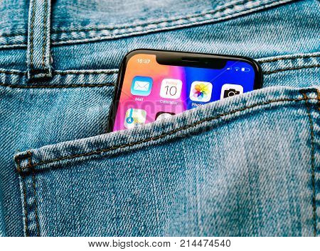 PARIS FRANCE - NOV 10 2017: New Apple iPhone X smartphone telephone mobile in pocket of fashion denim jeans pants trousers with home screen apps
