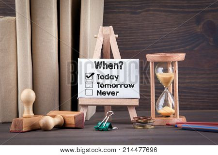 Choosing the right date - time management concept. Sandglass, hourglass or egg timer on wooden table showing the last second or last minute or time out