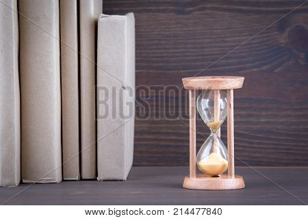 Sandglass, hourglass or egg timer on wooden table showing the last second or last minute or time out.