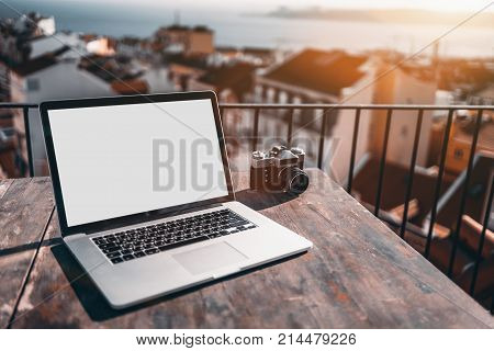 Mock-up of empty screen of modern notebook standing on wooden table outdoor on balcony; laptop with blank white screen template and vintage film photo camera near defocused cityscape in background