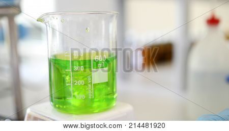 Laboratory glassware on a stirrer. Mechanical stirring, liquid of blue color is mixed in a round flask.