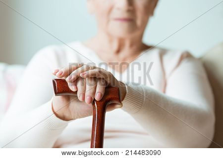 Elder Holds Hands On Walking Stick