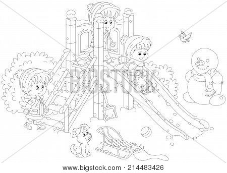 Little children playing on a slide at a playground in a winter park