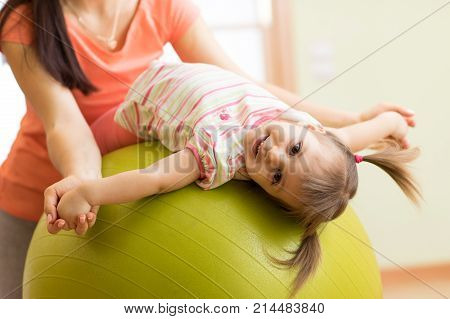 Cute kid girl stretching on pilates fitness ball with mother in gym
