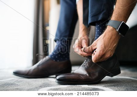 Unrecognizable businessman dressing up in a hotel room. Man tying his shoelaces. Close up.