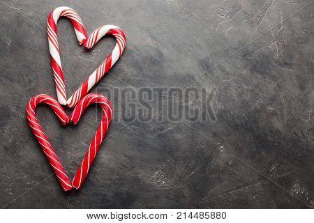 Peppermint Candy Canes In Heart Shapes On Black Concrete Background. Christmas Background. Top View