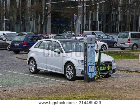 Budapest, Hungary - March 27, 2017: Charging modern electric Audi E-Tron car on the off-street parking from electric vehicle charging station. Eco-car of the future, environmental protection concept