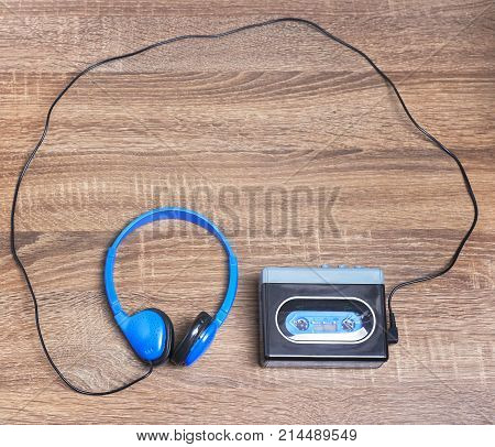 Vintage walkman and headphones on the wooden background