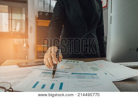 Businesswoman Using Pen Pointing Overview Graph Sheets At Her Working Space, Business Concept