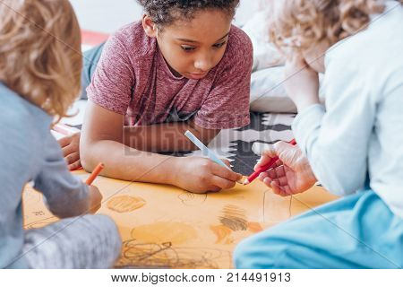 African-american boy drawing with his classmate during art classes in preschool