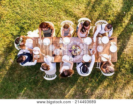 Wedding reception outside in the backyard. Bride and groom with a family around the table. Aerial view.