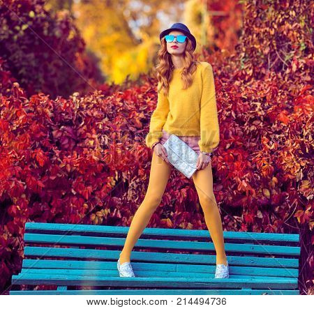 Fall Fashion. Young Woman Sitting on Bench in Sunny Colorful Park. Enjoy Nature, Urban Outdoor. Redhead Model in Stylish fashion Autumn Outfit. Girl in Trendy Jumper