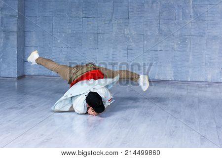 Yong modern style dancer in movement. Yong man in trendy clothes dancing brak dance on grey floor. Street dance concept.