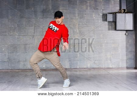 Young freestyle dancer on grey background. Young bold rap dancer in action on grey studio background.