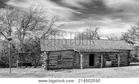 Pioneer log cabin with outdoor fireplace for cooking and antique bell for calling people to the house