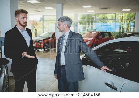 Handsome man at auto showroom talking with vehicle dealer. Car sale, sales manager showing cars to a buyer.