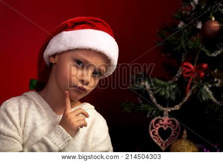 Cute Angry Girl In Fur Santa Claus Hat Near The Christmas Holiday Tree Thinking About The Gift With