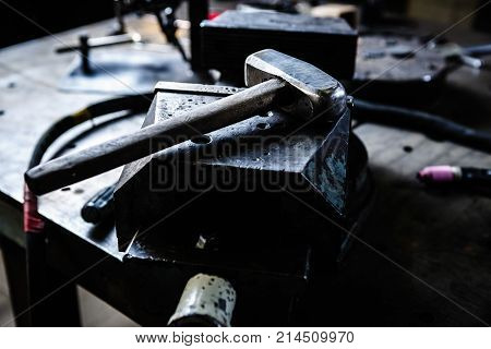 Hammer on anvil in smithery workshop.Professional blacksmith work table with incus for stamping metal products.Manual labor background.Welder worshop tools for metal manufacturing