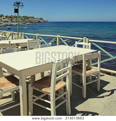 Outdoor greek cafe terrace with white tables and chairs overlooking the sea, Crete, Greece. Square toned image.