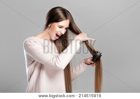 frustrated young woman combing tangled long natural hair with hairbrush