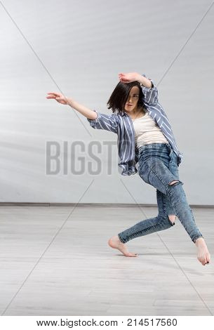Young urban woman dancing. Young beautiful dancer girl in dynamic pose on studio background. Modern dance education school.