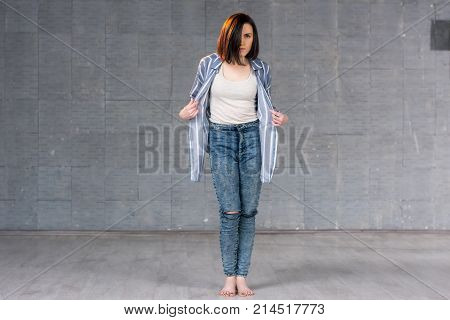 Young beautiful girl posing on studio background. Pretty young dancer wearing stylish jeans and shirt on studio background. Talented and artistic female performer.