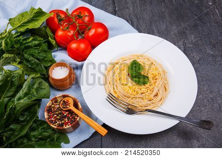 On the table in a white plate portion with pasta and cheese, cherry tomatoes, greens and spices.