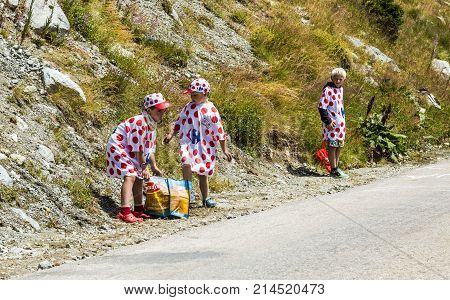 Col de la Croix de Fer France - 25 July 2015: Kids in Polka-Dot Jersey sorting the gists after the passing of the Publicity Caravan on the road to the Col de la Croix de Fer in Alps during the stage 20 of Le Tour de France 2015.