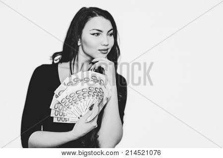 Young girl with a lot of euros in hand. Gold-digger. Black and white backround