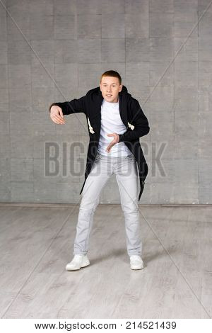Young rapper on studio bakground. Teenager hip-hop dancer posing on grey studio background. Talented and skillful young street dancer.