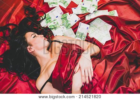 Lying pretty face woman under red blanket on the bed with 100 euro banknotes. Prostitute.