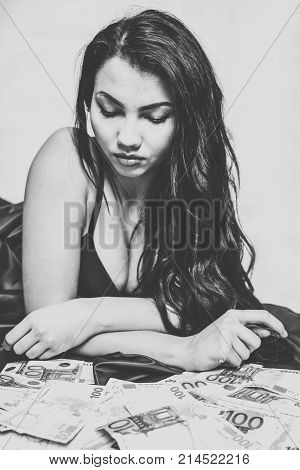 Young girl with a lot of euros in hand. Gold-digger. Prostitute. Black and white photo