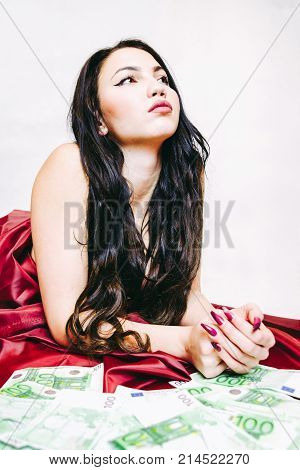Lying woman on the bed with 100 euro banknotes. Prostitute.