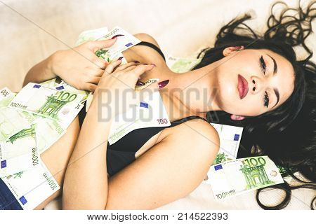 Lying woman under blanket with 100 euro banknotes