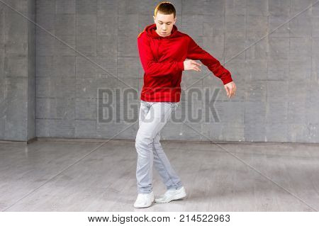 Young male modern dancer dancing. Modern style dancer in red sweater dancing brake dance over grey background. Young talented freestyle dancer.