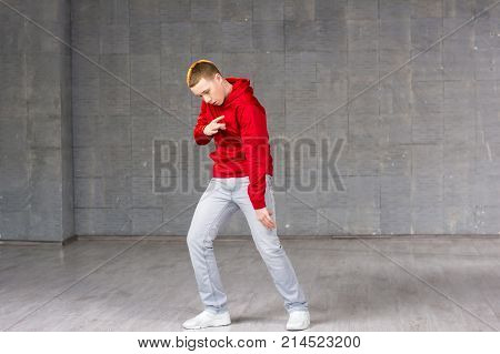 Skillful young dancer in movement. Young modern style male dancer performing hip-hop dance on studio background. Stylish and talented caucasian dancer boy.