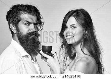 young happy smiling couple of sexy woman with long hair and handsome bearded man with beard in shirt drinking tea or coffee from cup in morning on grey studio background closeup