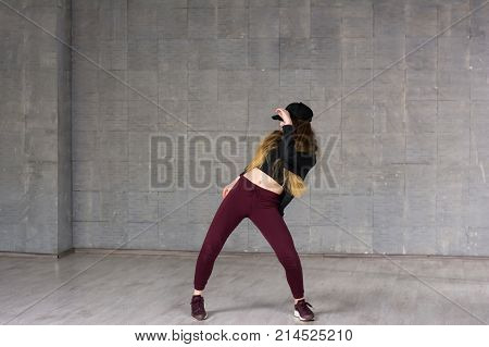Young girl dancing contemporary dance. Young slim girl performing modern dance on grey studio background.